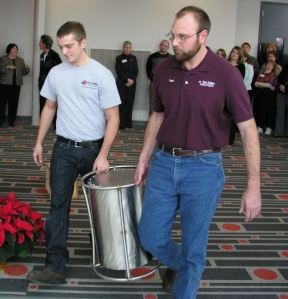 Industrial Welding Technician student Kyle Prellwitz (left) and Instructor Trent Schloss carry the sealed time capsule to its storage location.